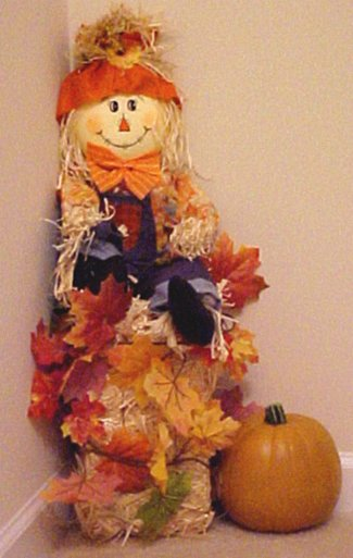 scarecrow sits on straw bale with leaves and pumpkin