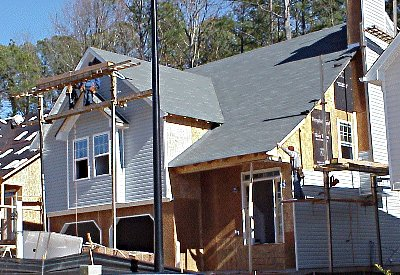 work crew putting siding on house